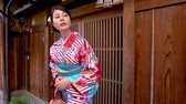 gueixa : elegant local woman in flower pattern kimono standing in front of wooden home waiting for friends join festival together. young japanese lady in traditional costume looking around carrying purse.