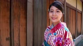 quimono : young girl tourist visit kyoto japan experience japanese culture wearing traditional clothing joyfully smiling to camera. female traveler in floral kimono cheerful standing in ishibe alley   in summer Stock Footage