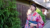 quimono : fast motion young local lady in floral kimono dress enjoy walking on stone old street in kyoto japan. green bamboo garden outside wooden traditional ancient house with red lanterns hanging on door