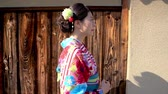 quimono : young local lady in kimono clothing walking along the wood and stone wall in old town kyoto japan under sunshine. japanese woman in traditional dress confident going home in sunset outdoors on street