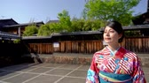 místní : local woman wearing japanese traditional clothing at Yasaka Pagoda and Sannen Zaka Street in Kyoto Japan after praying in temple. young lady in kimono cardigan standing under blue sky in spring.