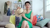 followers : Beautiful asian woman blogger is showing fashion straw hat in front of camera to recording vlog video live streaming at home. Business online influencer on social media concept. Stock Footage