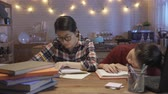 dormitory : female college student fall asleep at desk in dining room with kitchen in background. lazy girl sleep on table while another smart woman in glasses hard working writing doing homework at night home.