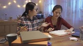 dormitory : Two asian girl students arguing about something on book at home kitchen.