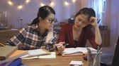 popa : young attractive and bored asian woman doing homework prepare for test at home.