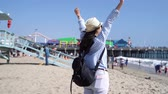 cankurtaran : Traveler woman with backpack standing on sandy beach arms open feeling freedom.