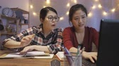 dormitory : Happy female college students discussing at home kitchen at night. young girl in glasses pointing to screen on laptop computer talking teaching her partner roommate typing on keyboard concept. Stock Footage