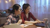 dormitory : two girl roommates team workers having discussion while doing report on final exam using laptop computer at home kitchen in midnight. friends talking pointing screen pencil another typing on keyboard