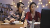 калькулятор : Group of university girl students working together on final project semester. young college female using laptop computer having discussion talking at night indoors. two hard-working woman at home.