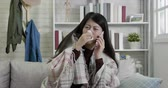 doku : slow motion of young lady call company boss in sick leave because of seasonal flu. ill woman sneezing talking on mobile phone request for day off. asian female having runny nose holding tissue cover. Stok Video