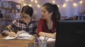 dormitory : two young beautiful Chinese Asian students girls smiling have video phone call with classmate team worker on laptop computer sit at wooden kitchen desk at home night. college ladies discuss online