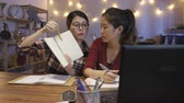 dormitory : group of asian college girl students discussing with teammates online on video phone call by laptop computer. woman in glasses showing notebook to classmate on screen at home kitchen at night. Stock Footage