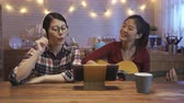 dormitory : two happy young woman friends having fun at home in modern kitchen sitting at wood desk playing music. Group of people girls enjoying their time in apartment smiling looking tablet use guitar singing