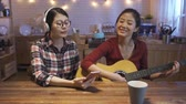 dormitory : young asian woman with headphones singing while her friend plays guitar. two music girls sitting in modern kitchen at home at night having fun together holding cellphone enjoy leisure time together.