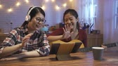 dormitory : female music band stay up late at home kitchen at night recording video upload on internet website new song. girls  waving hands to tablet computer playing guitar singing to audience online. Stock Footage