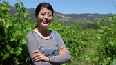 olgunlaşmamış : proud young asian woman farmer standing with folded arms in vineyard background. young satisfied female winemaker looking face at camera smiling crossed hands. confident owner of farm outdoor