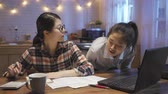 dormitory : sad depressed young asian business woman returning apartment from work tired sitting at kitchen table talking chatting with roommate. girl accounting expense at night waiting for friends coming home.