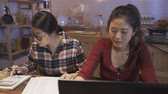 dormitory : young happy relaxed friends roommates at home kitchen table doing domestic debt accounting and calculating tax paperwork with bank paper and laptop computer. asian girls talking about month expense.
