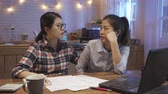 dormitory : Young woman friend comforting depressed roommate at kitchen table at home in late night while talking about work trouble.