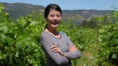 vinařství : Successful chinese female owner of vineyard standing on sunny day crossed arms side view face camera smiling attractive.