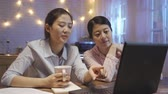 dormitory : young girls in smart casual sitting at kitchen table at night discussing about work on laptop.