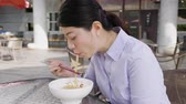 udon : Young asian business woman sitting outdoors cafe and eating instant noodle soup for lunch.