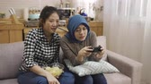 malaio : asian girl teaching Malay roommate with traditional costumes playing video games on tv
