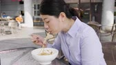 udon : slow motion of asian woman sucking spaghetti by chopsticks in outdoor cafe restaurant in italy.