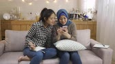 malaio : happy relax multi female friendship at home. malay woman talking telling news on smart phone sharing with korean girl who hard working doing homework on couch. two asian ladies discuss on cellphone Stock Footage