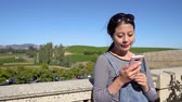 korkuluk : beautiful asian girl using cellphone smiling enjoy sunlight on face with landscape of vineyard in background. young woman tourist with sunglasses leaning on railing chatting online on mobile phone.