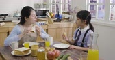 dona de casa : asian family having breakfast before little girl goes to elementary school. cute daughter kid in uniform sitting eating mom homemade croissant cheerful talking. elegant mother listening with toast.