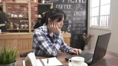 request : asian barista prepare coffee working order concept. Young successful business woman sitting in cafe bar with laptop and notebook. female in thought held her head looking at laptop screen intently.