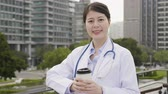 zábradlí : elegant nurse in lab coat and stethoscope with city skyscraper and park in background. Dostupné videozáznamy