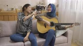 malaio : Two funny girls friends singing with microphone and playing electric guitar. multi woman chinese and arabian having fun sitting on sofa enjoy melody at home living room. happy female moving body.