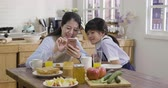 kruvasan : slow motion happy family. Young japanese mother and daughter girl playing on cellphone in morning kitchen with breakfast on table before school. Funny mom and child in uniform having fun smart phone. Stok Video