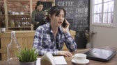 waitress : asian girl freelance angry and shocked talking on smartphone. stressful woman worker with laptop mad argue on cellphone in cafe bar. young female waitress busy making coffee in background in day time Stock Footage