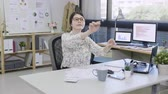 asa : crazy funny woman thoughtful imagine conducting an orchestra sitting at office desk close eyes enjoy music. young happy relax music lady work in company daydreaming. beautiful female worker hold pen Stok Video