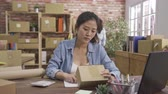 spuštění : two asian women freelancer friends work at home office online shopping business. young girl sitting typing on laptop computer checking cardboard boxes number of products writing. lady coworker walk Dostupné videozáznamy