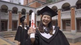 diplôme : slow motion asiatique japonais joyeux college woman student standing in front camera in campus traditional red brick building and cheering successful hold diploma with fist gesture on graduation day.