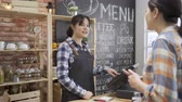 čtenář : asian female regular customer patron making payment through mobile phone at counter in cafe bar. waitress barista in apron using pos machine checking order. bank app cellphone buying paying purchase