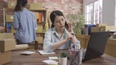 online store : smiling young asian woman owner and coworker in package shelf. online shop seller at home office talking on smart phone with customer. girl manager telling colleague new idea after hang on phone call