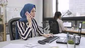 malaio : islam female leader with scarf religion pick up phone call on cellphone typing on computer talking with customer. japanese employee coworker helping manager record down writing on notebook teamwork