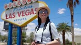originales : Happy young woman in straw hat and sunglasses cheering by Fabulous Las Vegas sign. Archivo de Video
