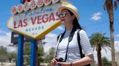 originales : Happy young asian woman visitor standing near Las Vegas Welcome sign.