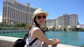 Невада : Travel girl backpacker leaning on railing on sunny day watching fountain in famous hotel in las vegas. Стоковые видеозаписи