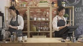 waitress : female shop assistant wearing apron using tablet after taking customer order in restaurant.