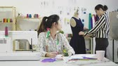 портниха : asian woman fashion designer coworkers working together in tailor shop.