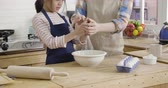 asian elegant mother is helping kid stir mix in bowl teaching talking on wooden table in kitchen with eggs and rolling pin. two parent and daughter in apron homemade making dessert DIY concept.