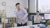 excited young asian business woman looking at male colleague dancing at office.