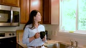 break : beautiful young woman worker get ready walk in kitchen holding mug drink coffee at traditional home.